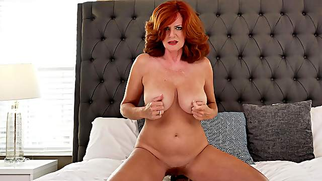 Curvy mature with flaming hair, seductive nudity in a sensual solo